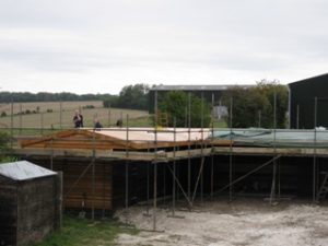 Stable roof showing the membrane being added to the roof